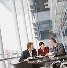 Businesswoman and Businessmen Sit at a Table on a Balcony Having a Discussion