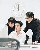 Business Colleagues Using a Computer in an Office and a Wall Clock in the Background