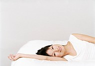 Woman Lying on One Side on a Bed With Her Arm Up