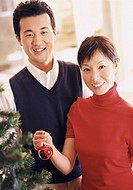 Couple Stand Holding a Christmas Bauble Next to a Christmas Tree
