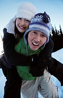 Young Couple Mess Around on a Ski Slope on Piggyback