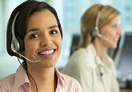 Portrait of a Woman Wearing a Headset with a Colleage in the Background