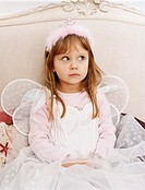 Girl Sitting on a Bed Looking Sideways Wearing a Fairy Costume