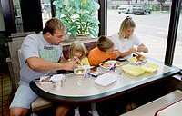 Family eating take out from containers with plastic utinsels on formica top table