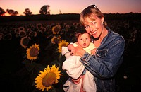 Mother with three month old daughter in sunflower field at sunset. USA