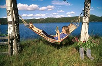 Reading a book in the hammock. Sweden