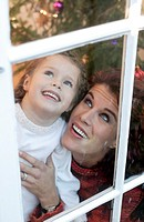mother and daughter looking out window, Christmas.