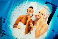 Two women wrapped in towels applying lotion