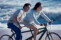 Young couple riding a tandem bicycle at the beach