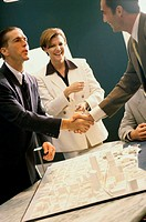 Business executives shaking hands at a presentation