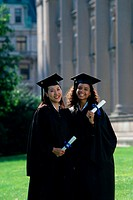 Portrait of two young women wearing graduation outfits holding diplomas