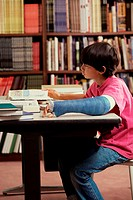 Boy sitting in a library and studying