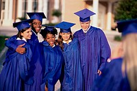 Group of students standing together wearing their graduation outfits