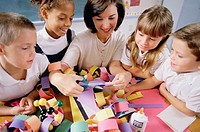 Female teacher teaching her students arts and crafts