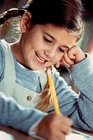 Smiling girl writing with a pencil