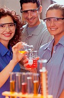 Portrait of two young women and a young man performing an experiment in a chemistry laboratory