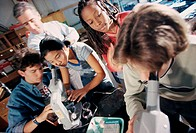 Teenagers looking through microscopes