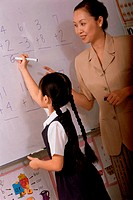 Girl writing on a board in class with a female teacher standing beside her