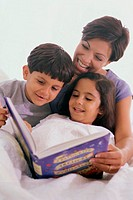 Mother and her two children reading a book