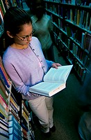 Teenage girl standing near bookshelves reading a book