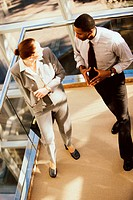 High angle view of a businesswoman and a businessman discussing in an office