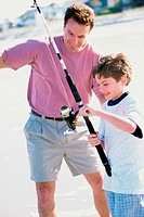 Father and son fishing on the beach