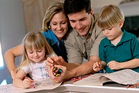 Parents and their children drawing in a coloring book