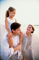Father and mother with their daughter on the beach