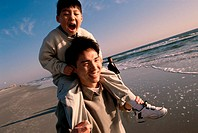 Close-up of a man carrying his son on his shoulders at the beach