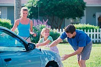 Parents and their daughter washing a car