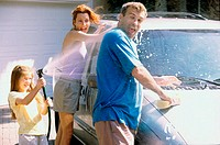 Daughter and her parents washing a car