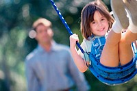 Close-up of a girl on a swing with her father standing behind