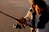 Close-up of a father and son fishing together