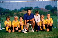 Portrait of a soccer team and coach on a field with a trophy