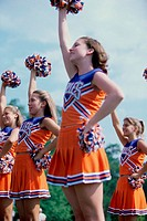 Side profile of cheerleaders with pom-poms
