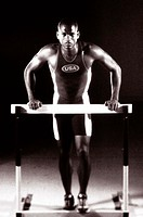 Portrait of a young man standing against a hurdle