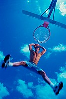 Low angle view of a young man slam dunking a basketball