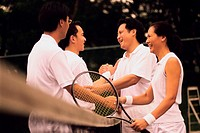 Side profile of tennis players shaking hands over a net