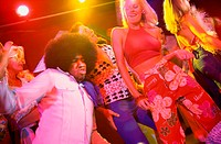 Low angle view of young men and women dancing in a discotheque