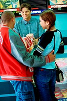 Teenage couple buying popcorn in a movie theater