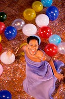 Portrait of a young woman dancing amongst balloons