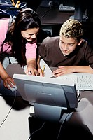 Teenage boy and a teenage girl in front of a computer monitor