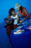 Young man playing a guitar on the beach with a young woman standing behind him