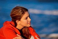 Side profile of a teenage girl sitting at the beach
