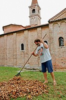 Monk gathering dead leaves at fall. San Francesco del Deserto monastery and church on the laguna. Venice. Italy