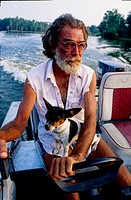 Halfpint the cajun and his dog Medor on their boat. Atchafalaya bayou and swamps. Louisiana. United states (USA)