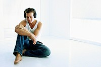 A man seated on the floor listening to music on headphones
