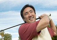 Smiling Man Swinging a Golf Club