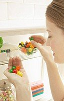 Woman Taking Jelly Beans out of a Cupboard