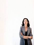 Businesswoman Standing with Her Arms Crossed Against a White Background